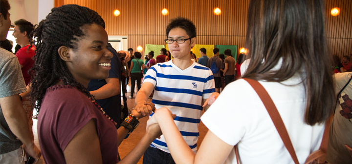 International students hold hands in a circle exercise