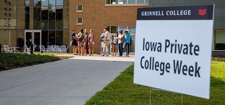 Prospective students and parents tour campus with Grinnell College Iowa Private College Week sign in foreground