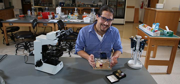 Kenji and his $10 microscope in the lab