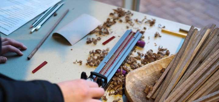 A student guides a hand-held planer to shave excess wood off a stick that's being transformed into a chopstick.