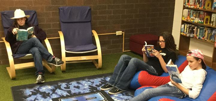Three middle-schoolers read in comfortable chairs around a brightly colored rug in a library