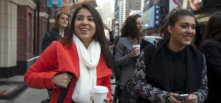 Woman in red coat holding coffee walks with group down New York street