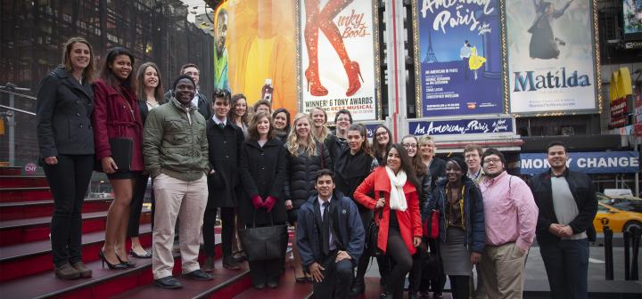 The travelers in a group portrait in front of large Broadway posters