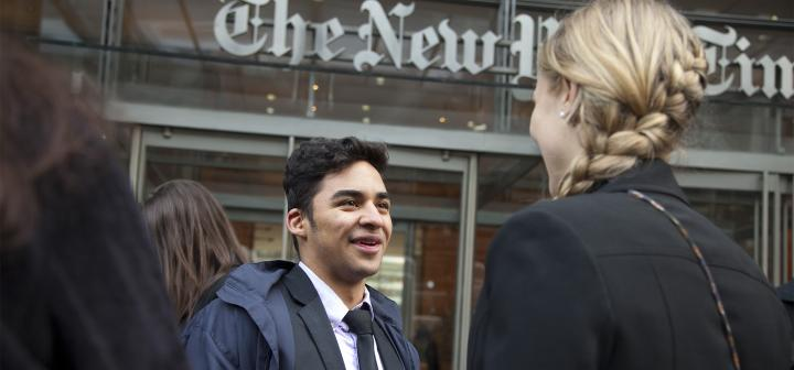 Two professionally dressed students talk in front of the New York Times entrance.