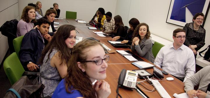 Students seated around a conference table listening to an off-camera speaker