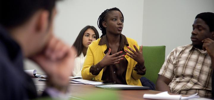 Young woman in yellow blazer gestures while talking to the speaker
