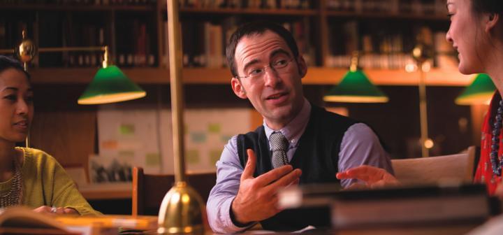 A professor leads a small seminar discussion