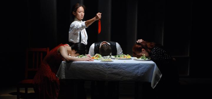 Actor holding red knife over table, while others sit with heads on filled plates