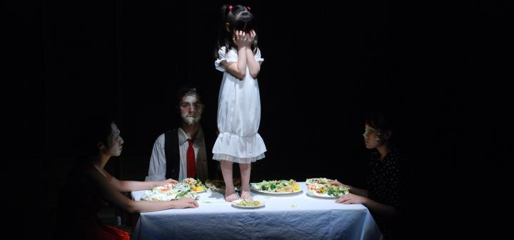 Small girl on table, with other actors seated around her, food on faces