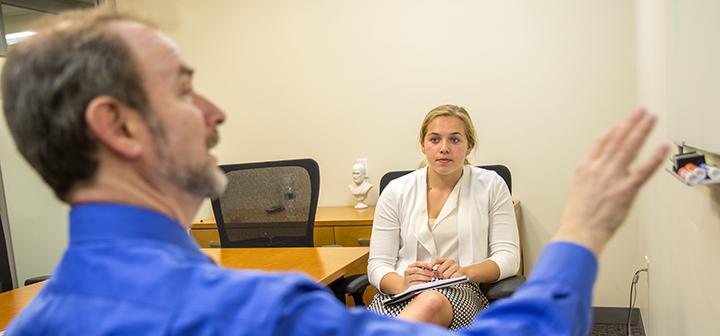 Michael Kahn '74 talks with a student during their internship at TIAA