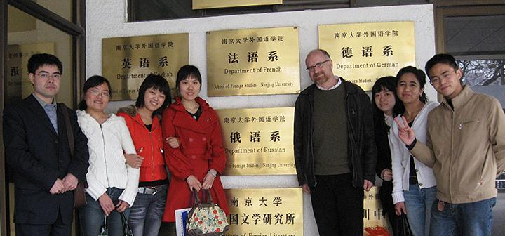 Students and professor in front of plaques listing departments