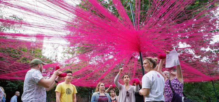 Participants string balls of yarn about poles, creating a brightly colored web of strings above themselves