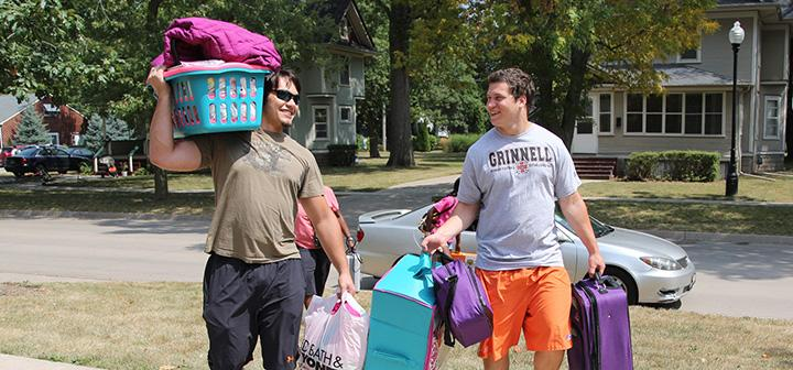 Two student athletes carrying belongings of a new student