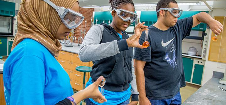 Students mix chemicals in flasks