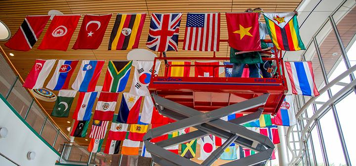 Facilities Management working on scissor-lift measuring space between flags.