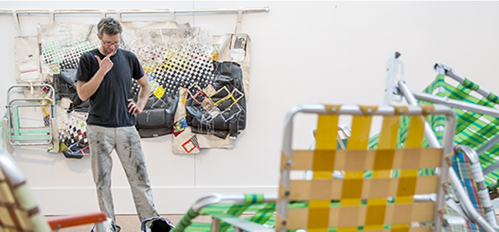 """Greg Smith sets up his exhibition """"Quality Uncertainty: The Market for Lemons"""" in the Faulconer Gallery."""
