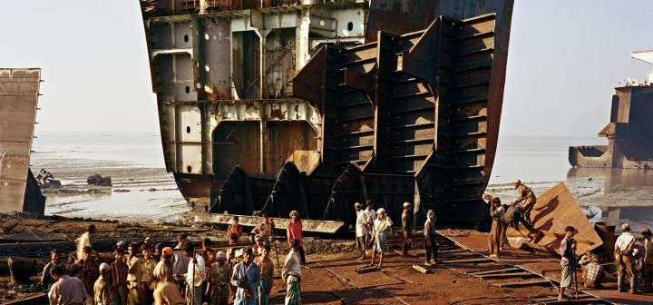 Workers standing at foot of a partially disassembled ship