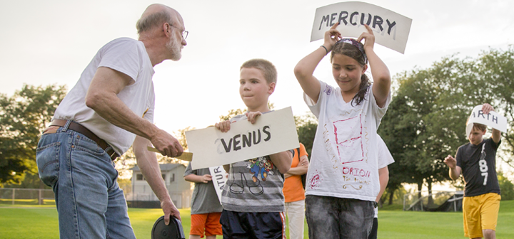 Kids hold up signs with the names of planets as Cadmus arranges them