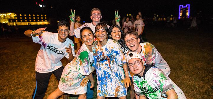 Students covered in paint grinning and striking a pose for the camera