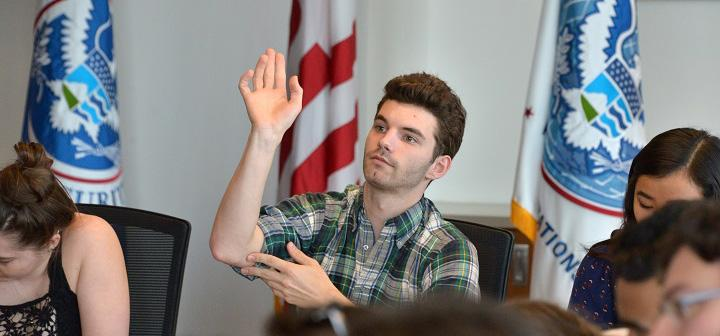 student raises hand, several flags in background
