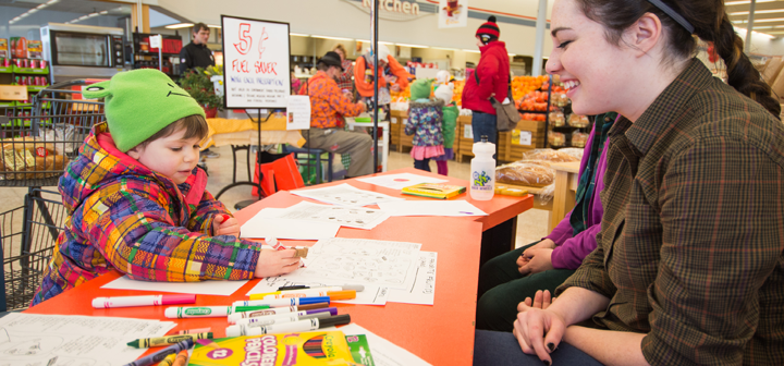 Child learns about healthy eating through coloring pages at healthy kids kiosk