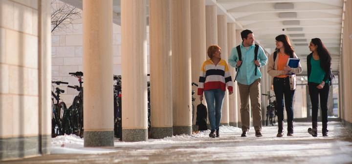 Four students walk through East Campus loggia