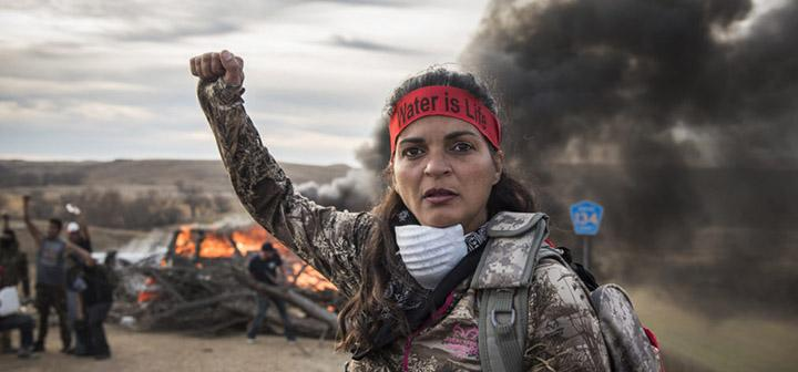 "Native American woman wearing ""Water is Life"" bandanna raises arm in defiance"
