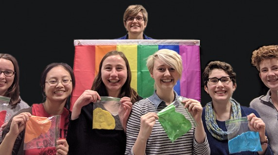Members of Out in STEM holding bags of a colored substance to match the pride flag behind them