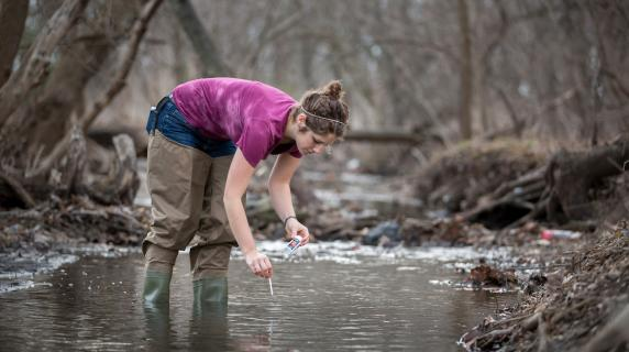 student collects water samples from creek