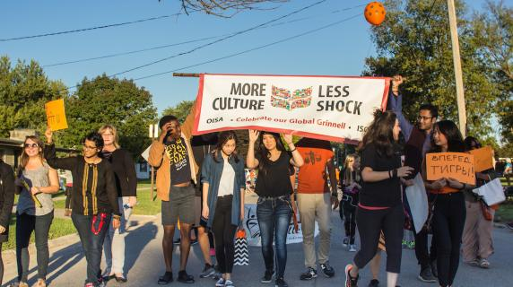 "students hold parade banner ""More Culture, Less Shock"""