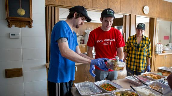 Food Recovery Network volunteers serve to local community meal