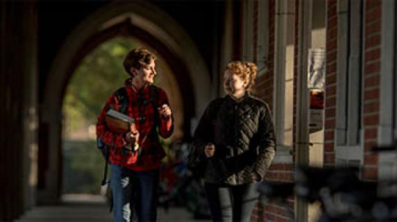 two students walking in the loggia