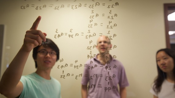 professor and students write equations on markerboard