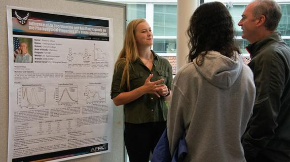 student presents research poster to faculty