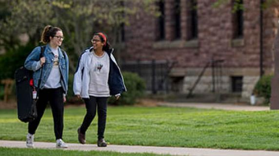 two students walk near Goodnow Hall