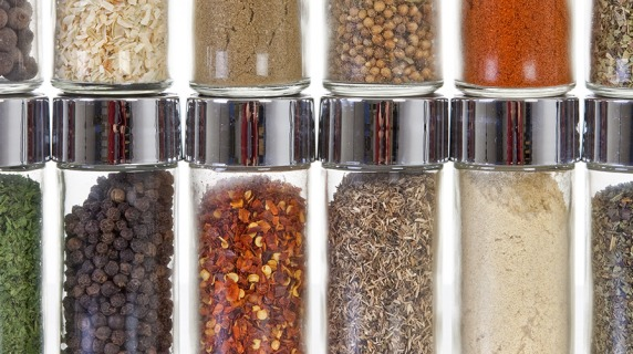 row of spices in small, clear glass jars