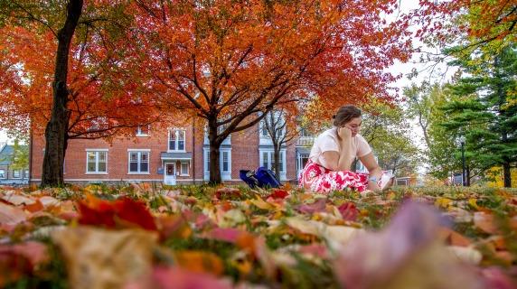 Student on grass during Fall.