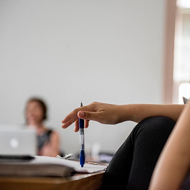 pen balanced upright with professor in background