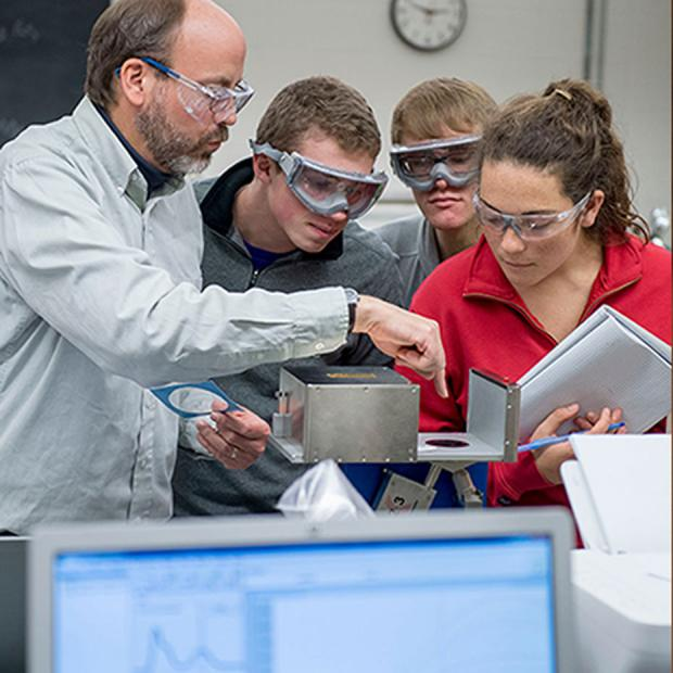 professor and students wearing goggles at equipment