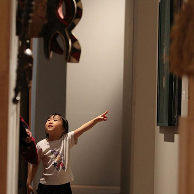 child points at painting in gallery