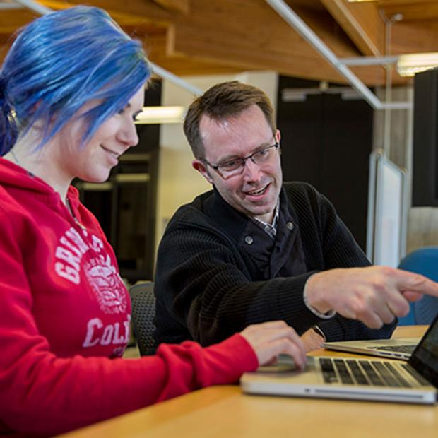 blue-haired student at a computer with professor