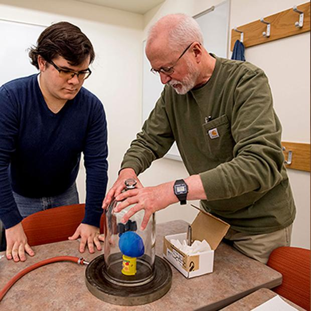 professor and student create a vacuum in a bell jar