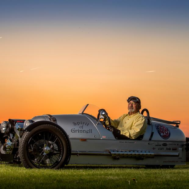 Will Freeman sits in his Morgan-Three Wheeler, named The Spirit of Grinnell, as the sun sets behind him
