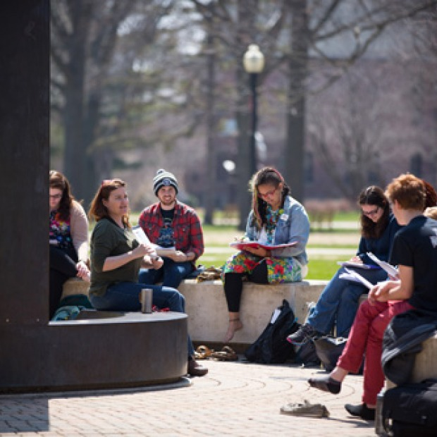 A class taking in some fresh air and meeting by the sundial outside of Noyce.