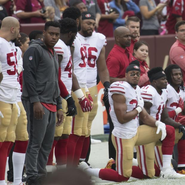San Francisco 49ers football players kneel during the national anthem