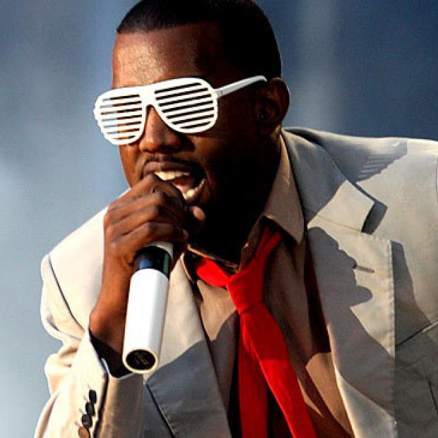 Kanye West in white grill glasses singing at a concert