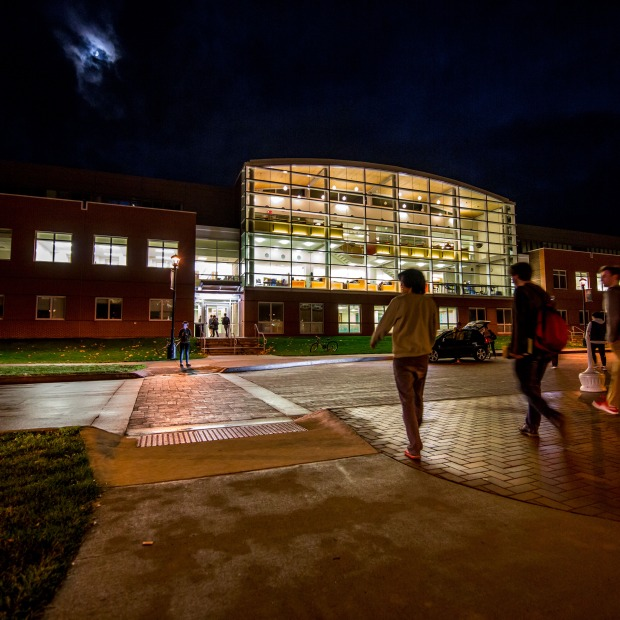 Students heading to a brightly lit Noyce Science Center at night