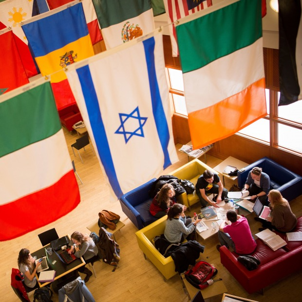 Students chat together under the global flags in Spencer Grill