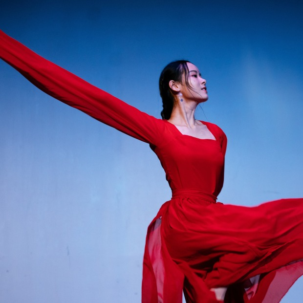A woman dances in a long and flowing red dress.