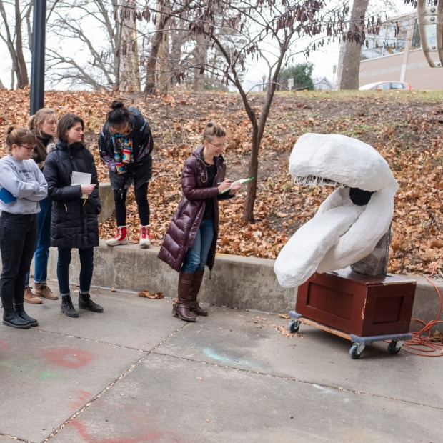 Students and Professor Lee Running critique a sculpture in an outdoor space